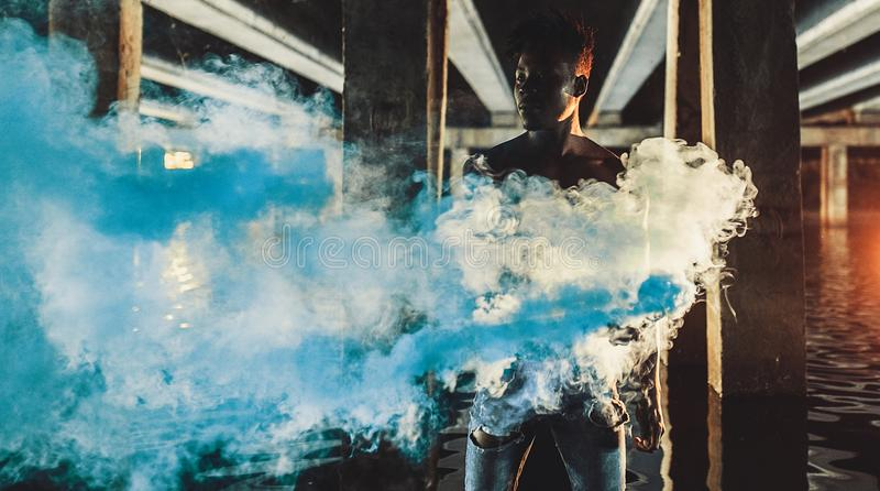 Young African man stands under bridge and holds colored blue smoke bomb royalty free stock photography