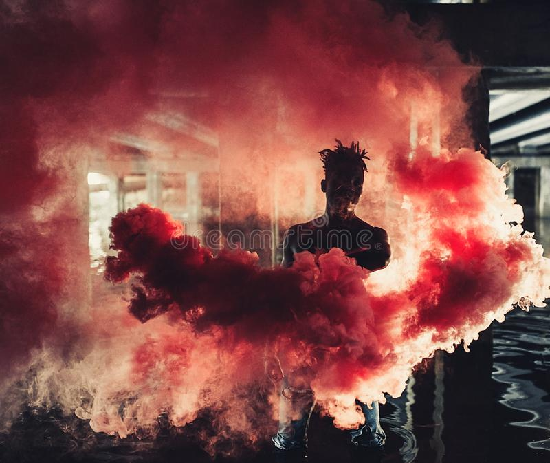 Young African man stands under bridge and holds colored red smoke bomb stock images