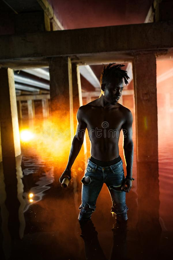Young African man stands under bridge and holds colored red smoke bomb stock image
