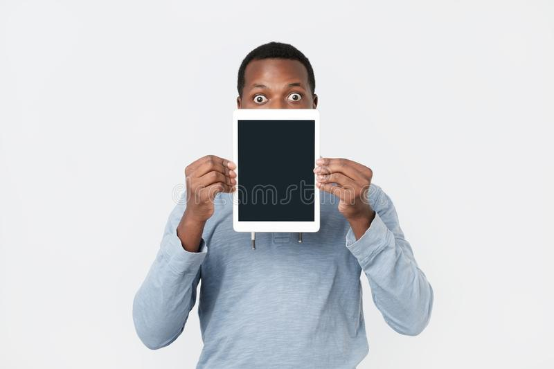 Young African man with tablet showing screen of modern tablet. stock photo