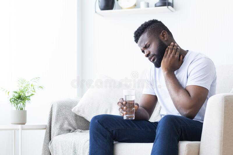 Young african man touching his neck and holding glass of water royalty free stock image