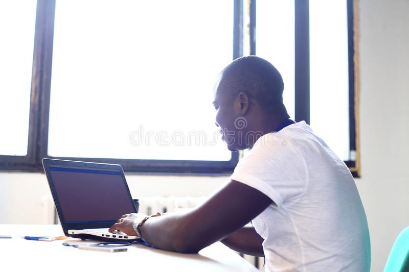 Full concentration. Close-up part of young African man using laptop while sitting at his working place. Young African man using laptop while sitting at his stock image