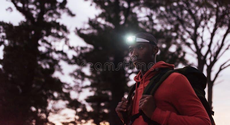 Young African man wearing a headlamp jogging at dusk stock photo