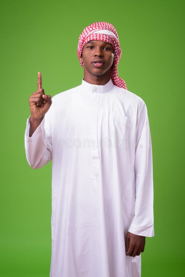 Young African man wearing traditional Muslim clothes against gre stock image
