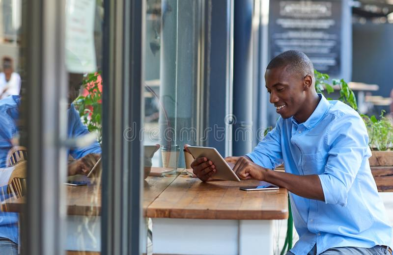 Young African man working online at a sidewalk cafe table stock photo