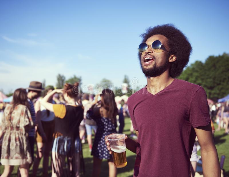 Young African man drinking beer at the festival. Young African men drinking beer at the music summer festival royalty free stock image