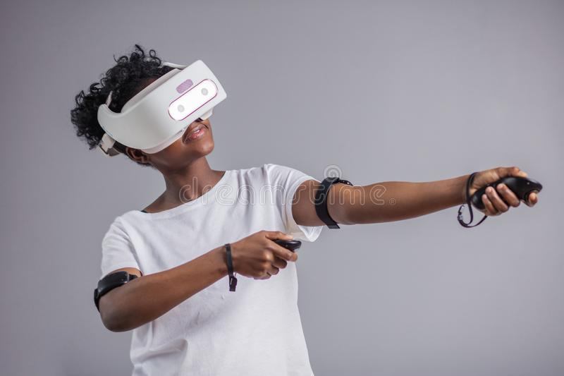 Young african student girl playing with virtual reality glasses. stock images