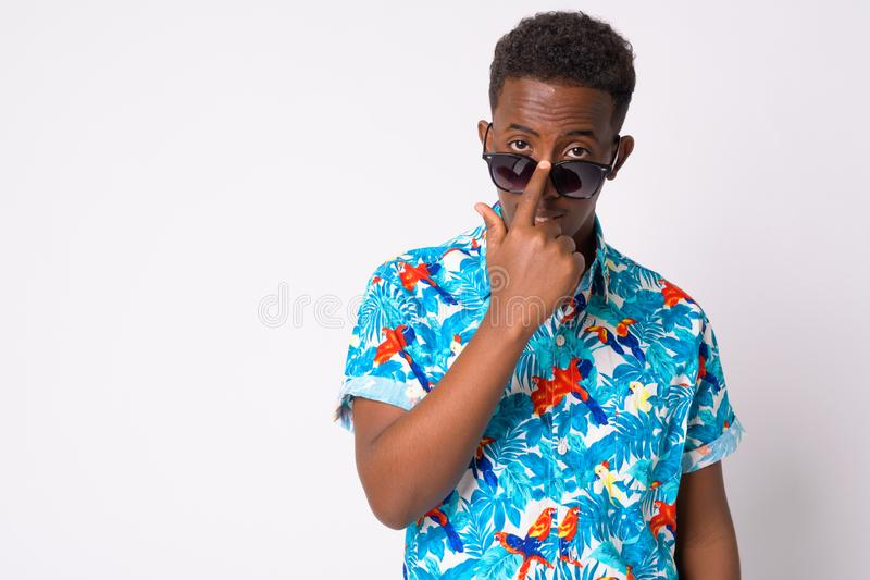 Young African tourist man with Afro hair peeking through sunglasses. Studio shot of young African tourist man with Afro hair against white background stock photography