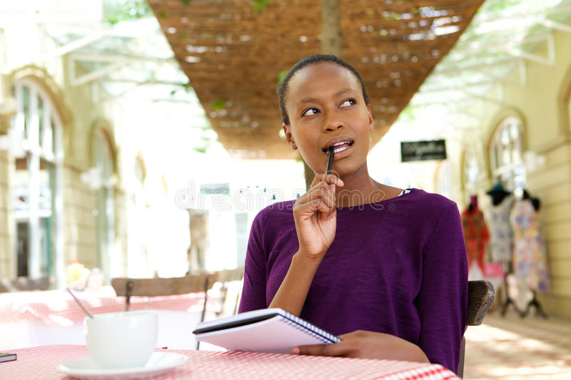 Young african woman at cafe writing notes. Portrait of young african woman sitting at cafe with notepad and looking away thinking royalty free stock photos