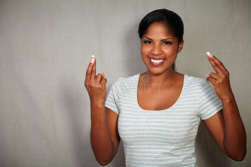 Young african woman crossing fingers while smiling stock photos