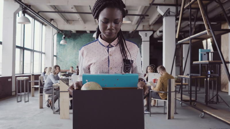 Young african woman getting fired from work. Female walks through the office, carrying box with personal belongings. Young african women getting fired from work stock images
