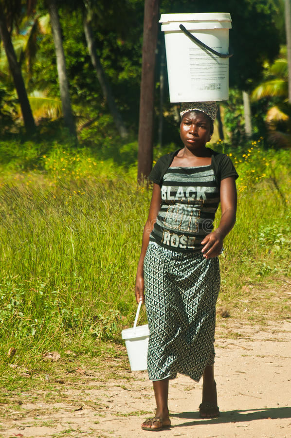 Young African woman going carrying supplies