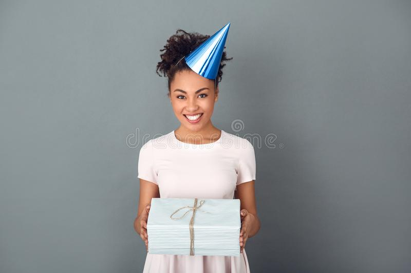 Young african woman on grey wall studio celebration concept holding present box royalty free stock images
