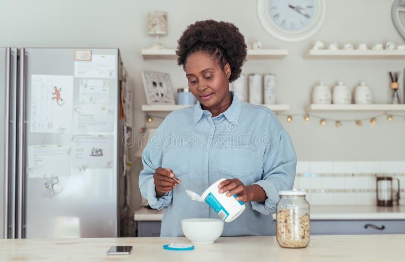Young African woman having yoghurt with her cereal for breakfast royalty free stock image