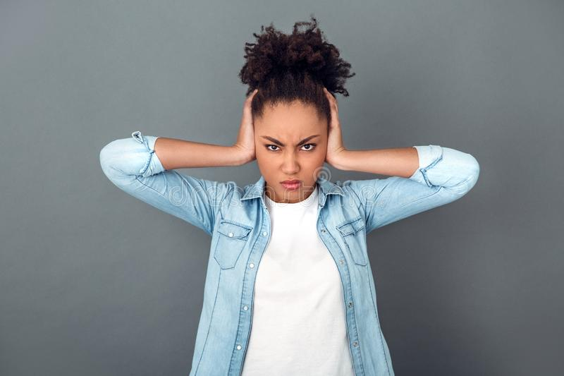 Young african woman isolated on grey wall studio casual daily lifestyle angry. Young african female student isolated on grey wall holding head looking camera stock photo