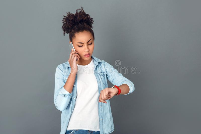 Young african woman isolated on grey wall studio casual daily lifestyle checking time. Young african female student isolated on grey wall talking with a boss by stock image