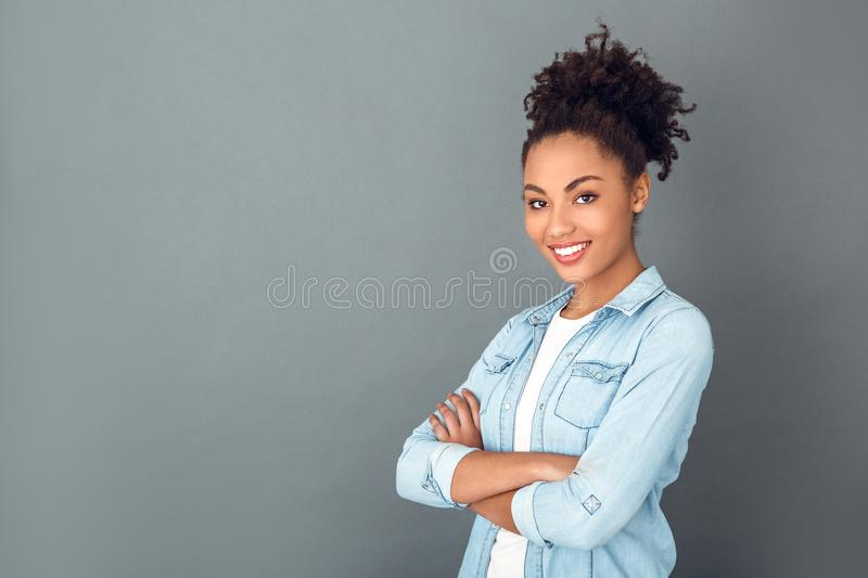 Young african woman isolated on grey wall studio casual daily lifestyle confident. Young african female student isolated on grey wall looking camera smiling royalty free stock photography