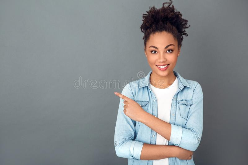 Young african woman isolated on grey wall studio casual daily lifestyle copyspace. Young african female student pointing at space on grey wall looking camera royalty free stock photography