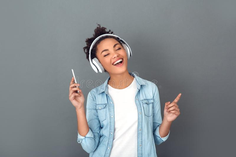 Young african woman isolated on grey wall studio casual daily lifestyle listening music royalty free stock photos