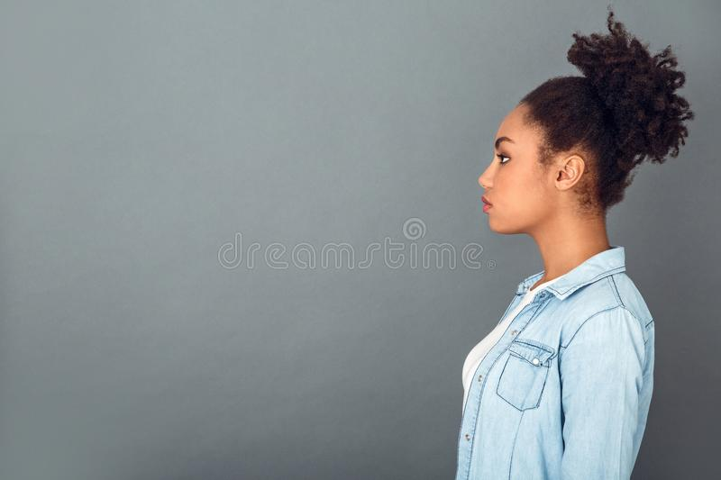 Young african woman isolated on grey wall studio casual daily lifestyle profile. Young african female student isolated on grey wall standing profile looking stock photos