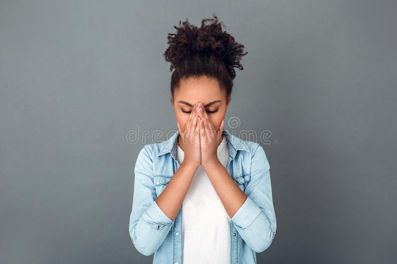 Young african woman isolated on grey wall studio casual daily lifestyle sneezing. Young african female student isolated on grey wall sneezing cover face with royalty free stock images