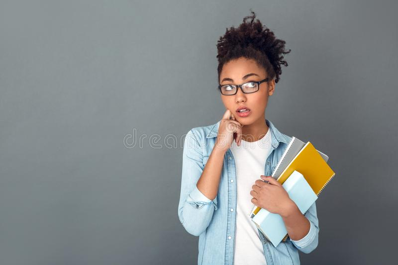 Young african woman isolated on grey wall studio casual daily lifestyle student confused. Young african female student isolated on grey wall wearing eyeglasses royalty free stock image