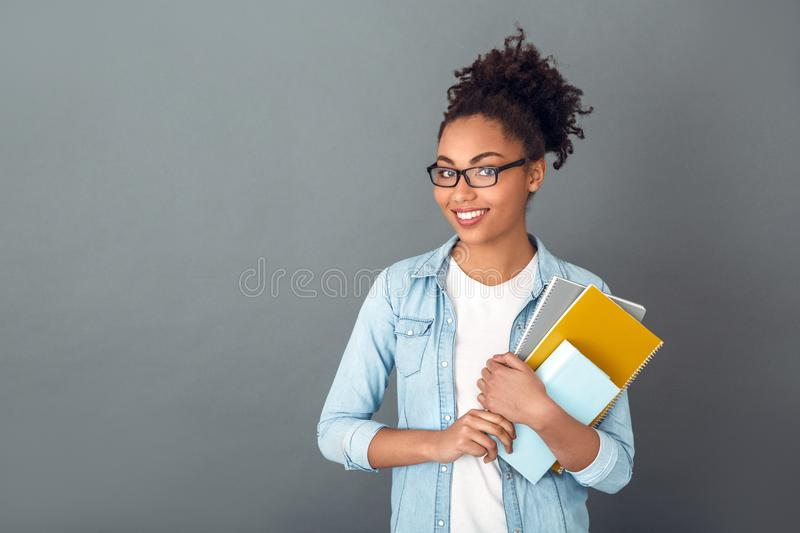 Young african woman isolated on grey wall studio casual daily lifestyle student holding notebooks smiling. Young african female student isolated on grey wall royalty free stock photo