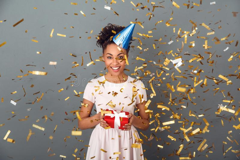 Young african woman isolated on grey wall studio celebration concept confetti burst stock photo