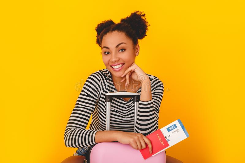 Young african woman isolated on yellow wall studio teen style traveler sitting on suitcase. Young african female teenager tourist isolated on yellow wall sitting stock image
