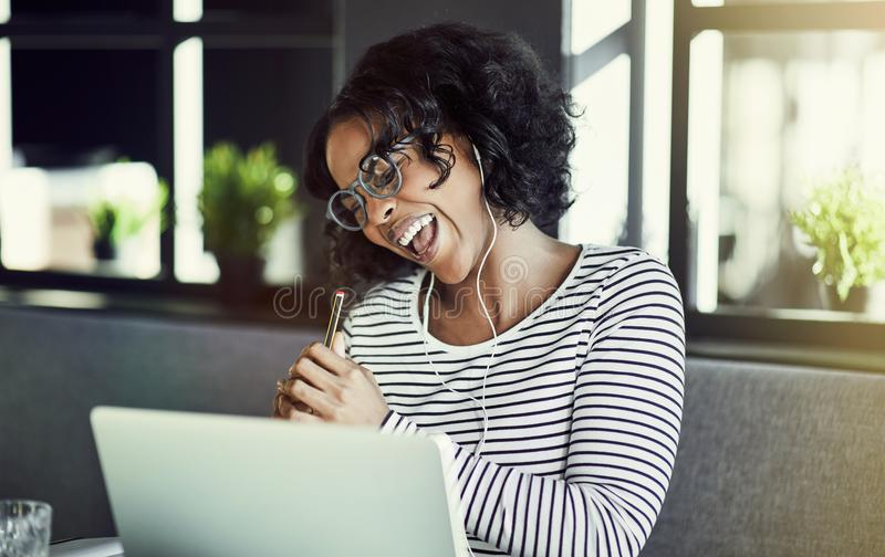 Young African woman laughing while enjoying an online chat stock photos