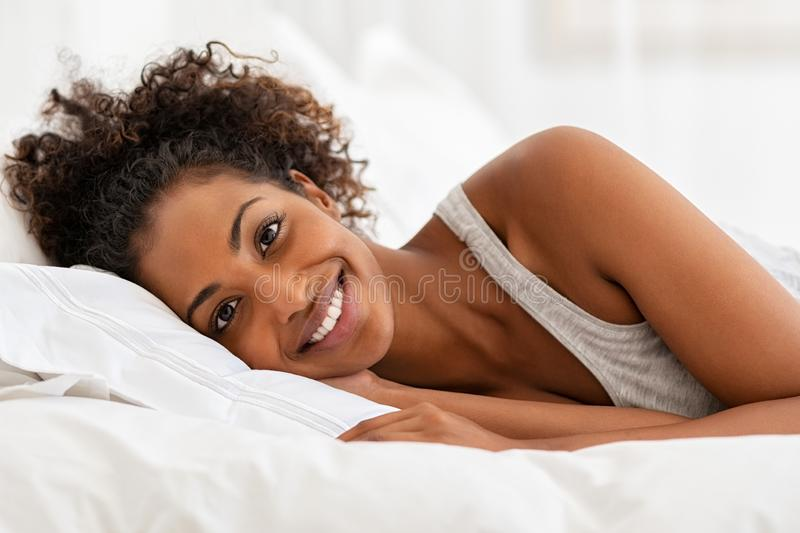 Smiling woman lying on bed looking at camera stock photo