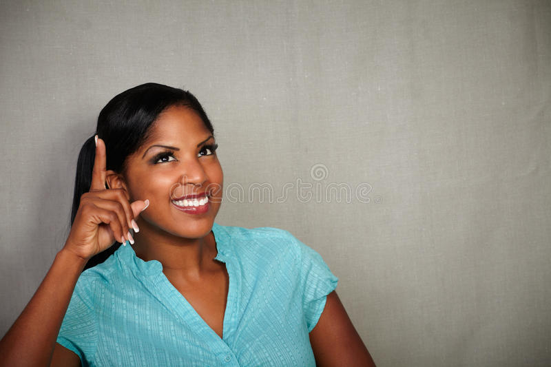 Young african woman pointing up while smiling stock photo