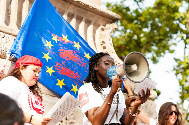 Barcelona, spain- 17 july 2019:  young african woman reading manifesto against far right eith european union flag with blood royalty free stock photos