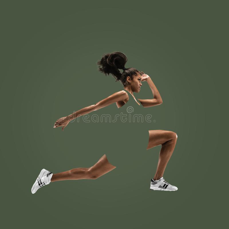 Young african woman running or jogging isolated on green studio background. stock image