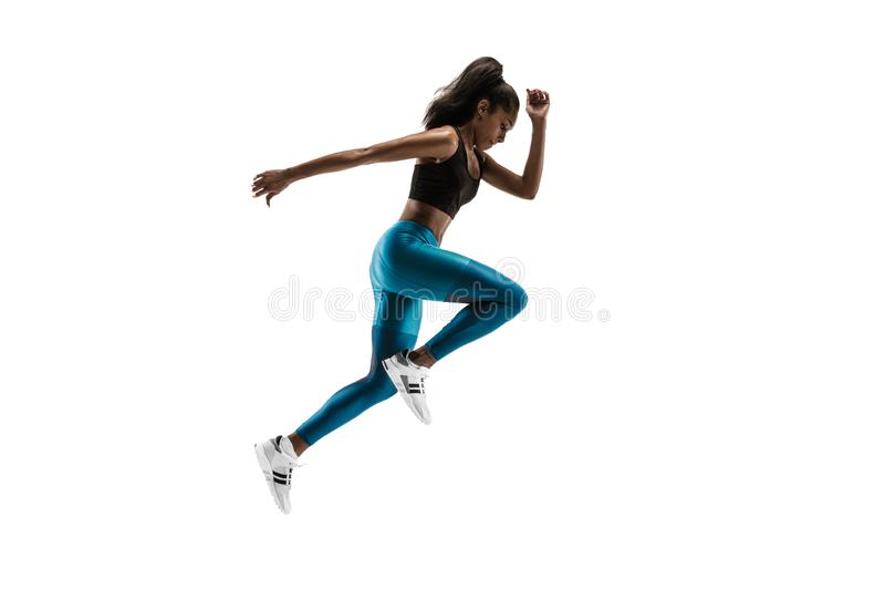 Young african woman running or jogging isolated on white studio background. stock photography