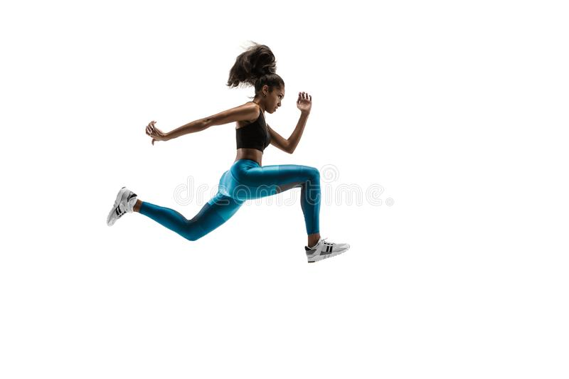 Young african woman running or jogging isolated on white studio background. stock image