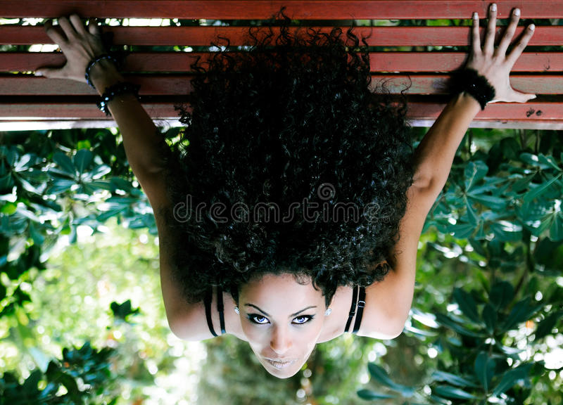 Young african woman siting on bench in park stock photo