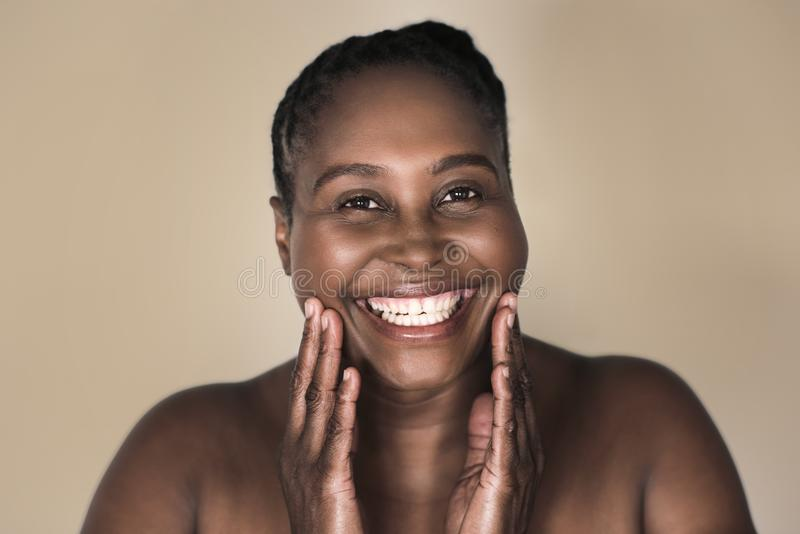 Young African woman smiling and touching her perfect complexion royalty free stock photo