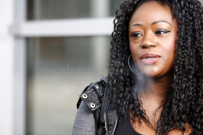 Young African woman smoking a cigarette. Exhaling smoke through her nostrils with an expression of satisfaction, close up head and shoulders royalty free stock images