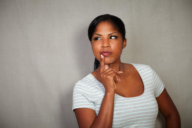 Young african woman thinking with hand on chin royalty free stock photos