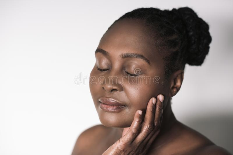 Young African woman touching her cheek against a white background stock images