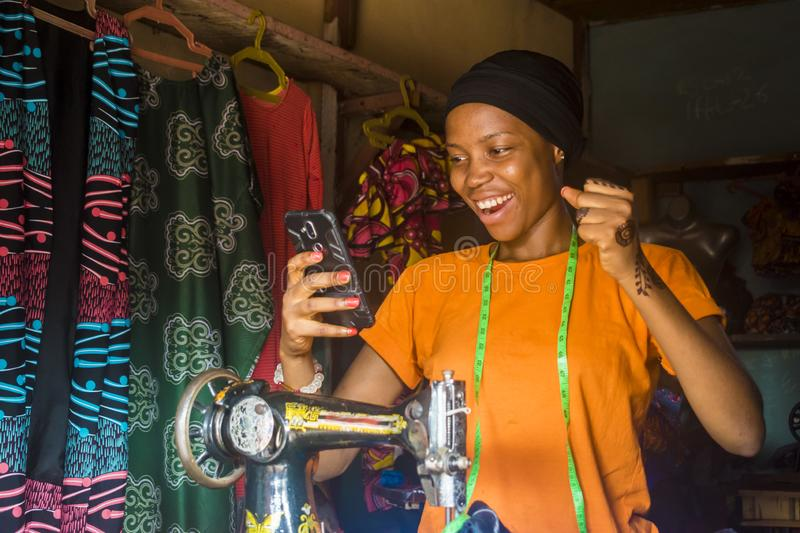 African woman who is a tailor feeling excited and happy and jubilant while viewing content on her mobile phone stock image