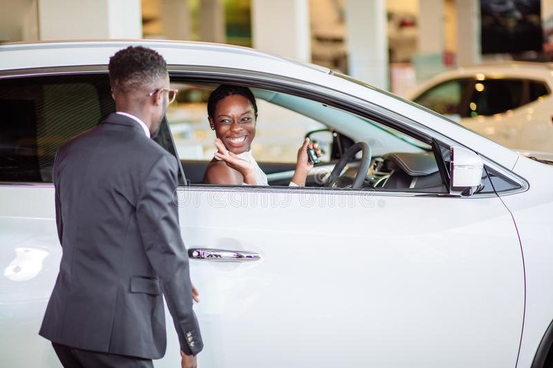African woman surprised by new car, gift for my beautiful wife royalty free stock image