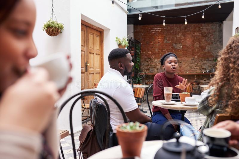 People talking together over coffee in a trendy cafe courtyard stock photo