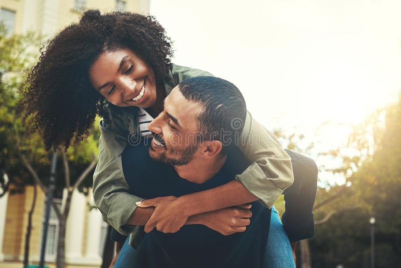 Young man carrying his girlfriend on his back royalty free stock image