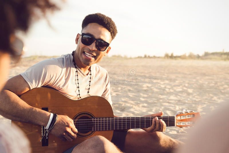 Young afro american man playing guitar for friends. While sitting on the beach stock photography