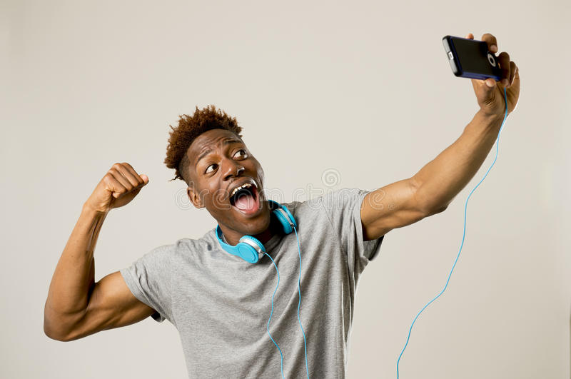 Young afro american man smiling happy taking selfie self portrait picture with mobile phone. Young afro american black man smiling happy taking selfie self royalty free stock image