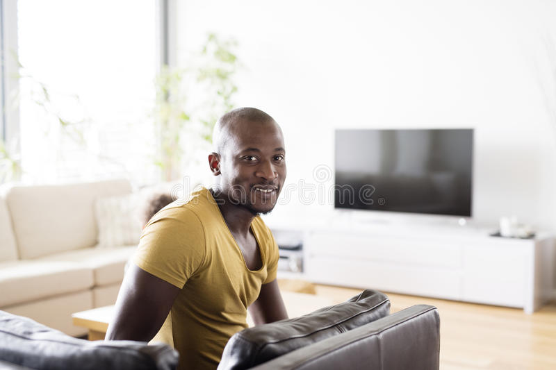 Young afro-american man in yellow t-shirt at home. Young handsome afro-american man in yellow t-shirt at home royalty free stock photos