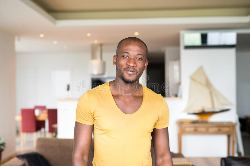 Young afro-american man in yellow t-shirt at home. Young afro-american man in yellow t-shirt at home, smiling royalty free stock photography