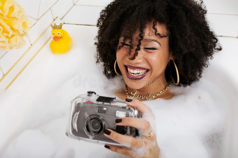 Young afro-american teen girl laying in bath with foam, wearing swag jewelry flawless, making selfie. Close up royalty free stock image